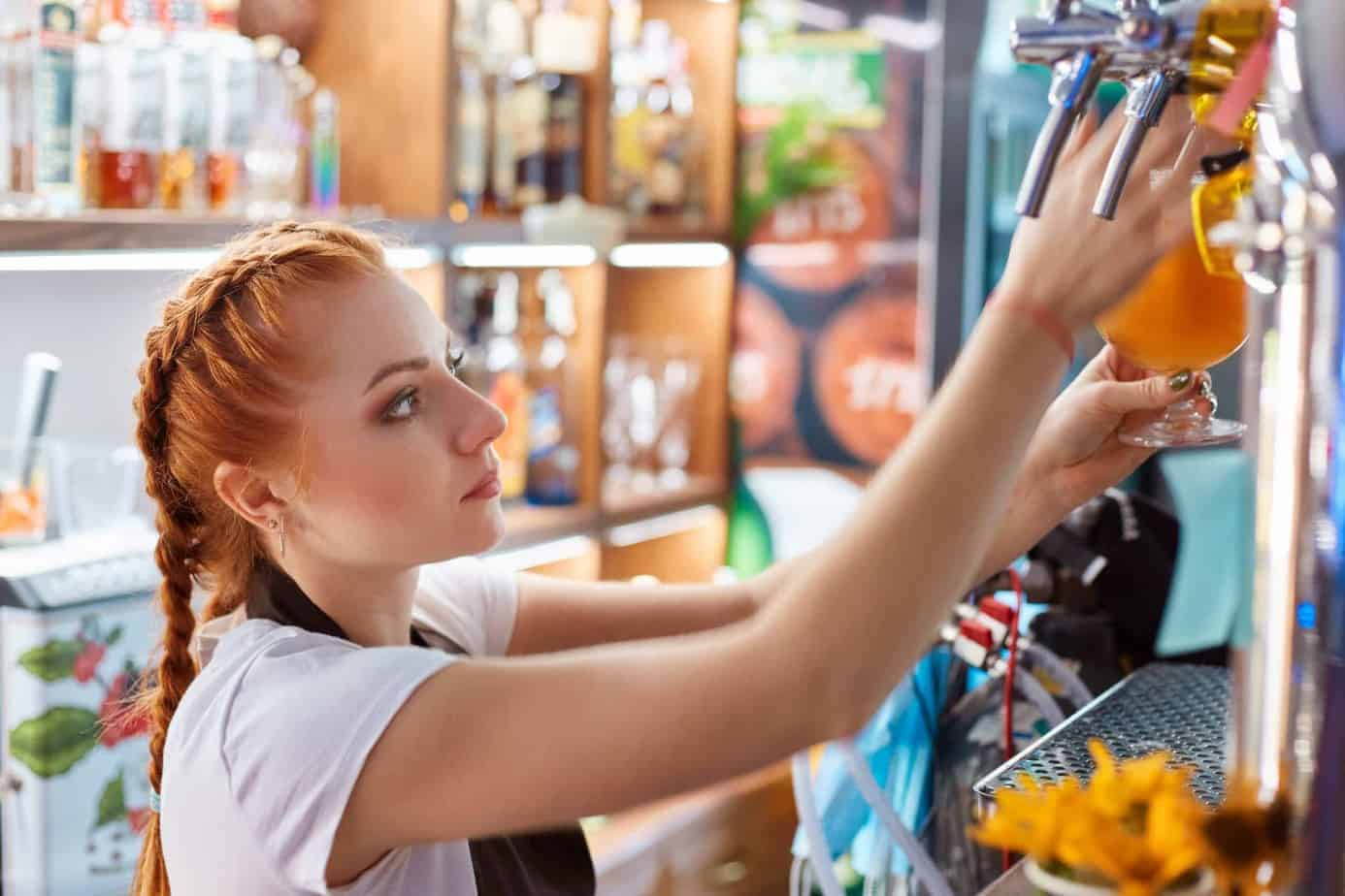 Female bartender tapping craft beer in bar, side view of red haired barman wearing white casual t shier and apron, looks serious, being concentrated on her work.